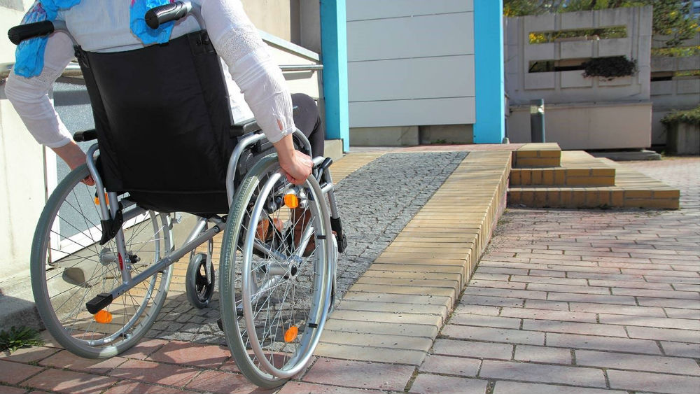 patient on a wheelchair entering a house